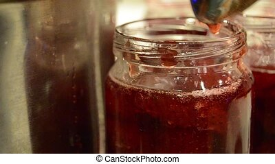 Woman Puts Handmade Strawberry Jam In Jar. close up