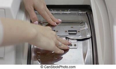 Woman puts laundry out of washing machine