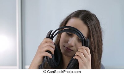 attractive woman puts on and takes off the headphones
