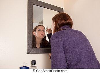 woman puts on eyebrow makeup
