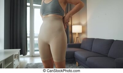 Woman puts on slimming underwear to improve body silhouette. Concept of aspiration for a perfect body