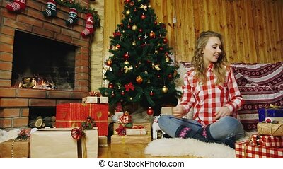 Woman puts presents under the Christmas tree