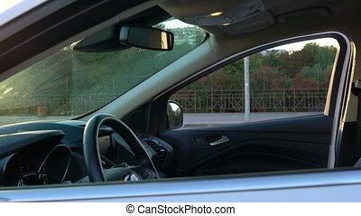Woman puts shopping bags on a car seat and sits in it,...