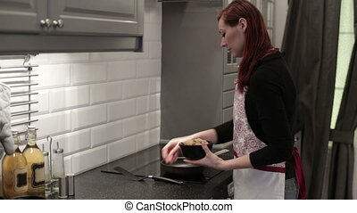 Woman puts shrimp in preheated frying pan