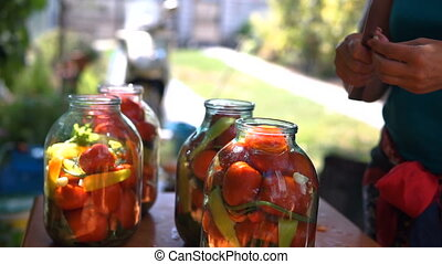 woman puts tomatoes in jar for preservation