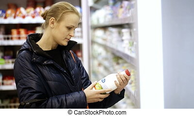 Woman putting a bottle of milk in her shopping basket -...