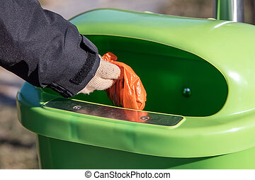 Woman putting a excrement bag from a dog into a waste bin...
