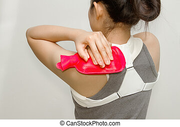 woman putting a hot pack on her shoulder pain