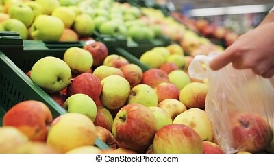 woman putting apple to bag at grocery store - shopping,...