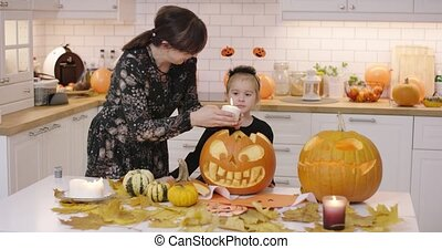 Woman putting candle into jack-o-lantern - Woman in glasses...