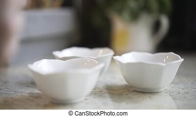 Woman putting candy in bowls with decoration