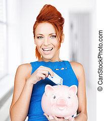 woman putting cash money into piggy bank