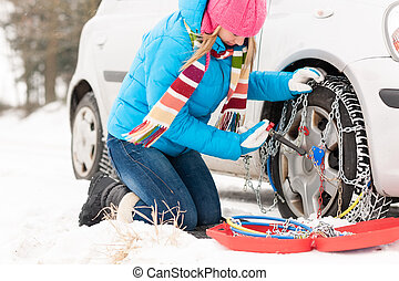 Woman putting chains on car winter tires - Woman putting...