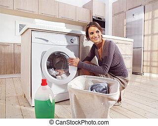 woman putting cloth into washing machine