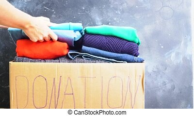 donation and charity concept - Woman putting clothes into...