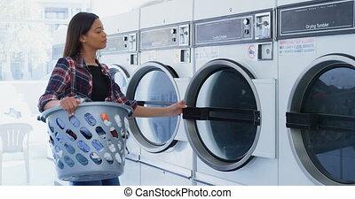 Woman putting clothes into washing machine 4k - Woman...