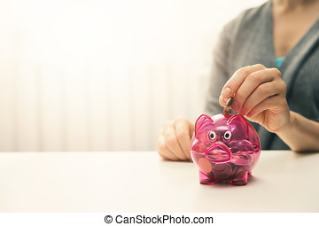 woman putting coin in piggy bank. copy space