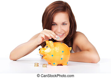 Woman putting coins in her piggy bank