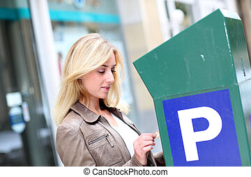 Woman putting coins in parking meter