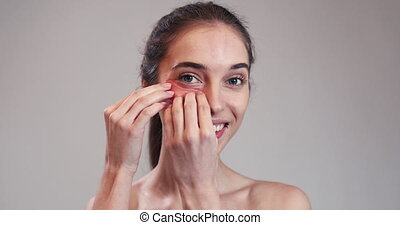 Woman Putting Collagen Pads under Her Eyes - Woman with...