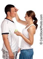 Woman putting cream on her boyfriend's face