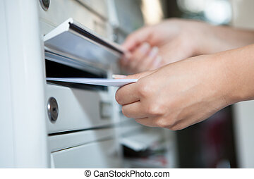 Woman putting envelope in mailbox - Close-up of woman's hand...