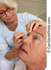 Woman putting eyewash in eyes of a man