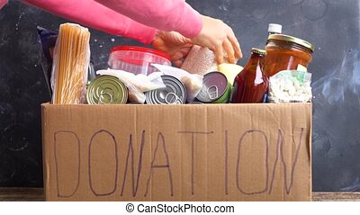 donation and charity concept - Woman putting food into...