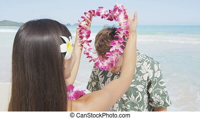 Young woman putting lei garland of pink orchids around man's neck at Hawaiian beach. Handsome male is in Aloha clothing. Happy couple is enjoying their summer vacation.