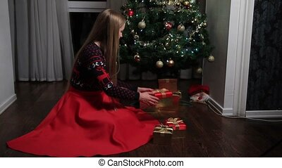 Woman putting gift boxes under Christmas tree