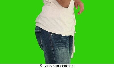 Woman putting her money on her back pocket against a green...