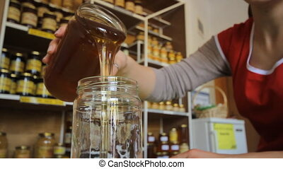 Woman putting honey in jar