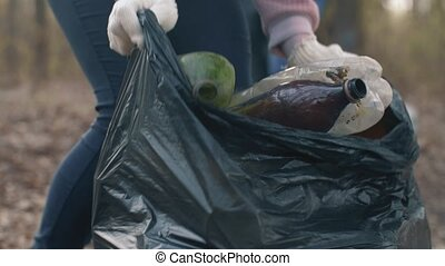 Woman putting household waste into bin bag