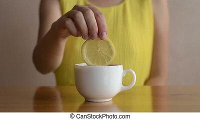 Woman putting lemon into tea