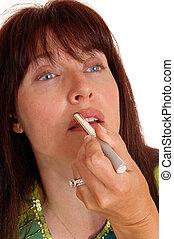 Woman putting lipstick on her lips D1:J37.