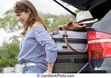 woman putting luggages in the trunk of a car