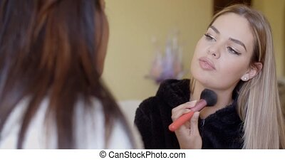 Woman Putting Make up to her Pretty Friend