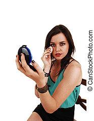 Woman putting makeup on.