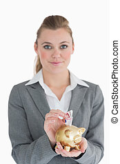 Woman putting money in the piggy bank