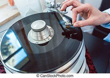 Woman putting needle on vinyl record on turntable