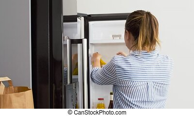 woman putting new purchased food to home fridge - eating and...