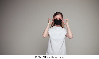 Stock video of a young Caucasian woman putting on black carbon facial mask to prevent virus contamination. Studio shot.