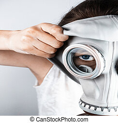 Woman putting on gas mask - Close-up of woman putting on gas...