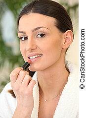 Woman putting on lip-stick