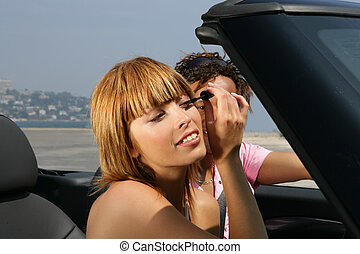 Woman putting on mascara in a car