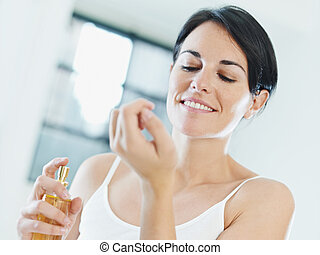 woman putting on perfume and smiling. Copy space