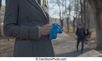 Woman putting on protective gloves