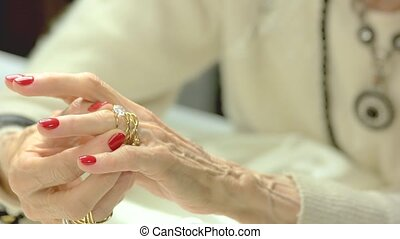 Woman putting on ring with diamond. Well-groomed hands with...