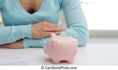 woman putting one euro coin into piggy bank - business,...