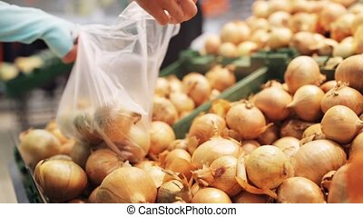 woman putting onion to bag at grocery store